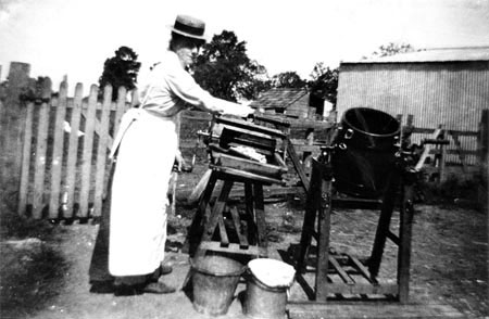A woman making butter outdoors c.1900.