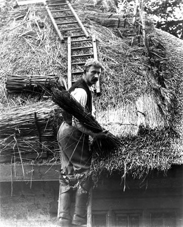 A man thatching, early twentieth century. The tools, material and processes of thatching have changed very little for hundreds of years.
