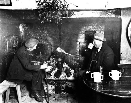Cider drinkers in a pub at Compton Dundon, c.1930s. Cider was often warmed up in pubs using a special container called a cider shoe. Spirits such as gin and brandy were added to the mixture. A tradition two handled cider mug was often used and can be seen on the table in this photograph.