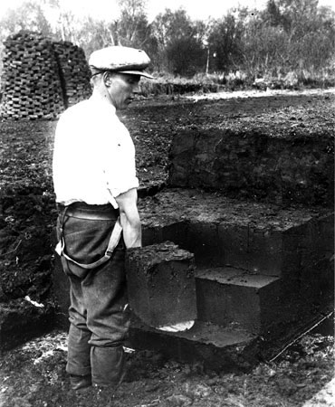 A man cutting peat. Note that the man is wearing puttees, not Wellington boots. Puttees were worn by agricultural workers together with hobnail boots, but were eventually made obsolete by cheap rubber boots.